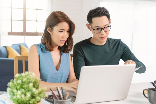 Serious asian husband checking analyzing statement utilities bills sitting together at home.