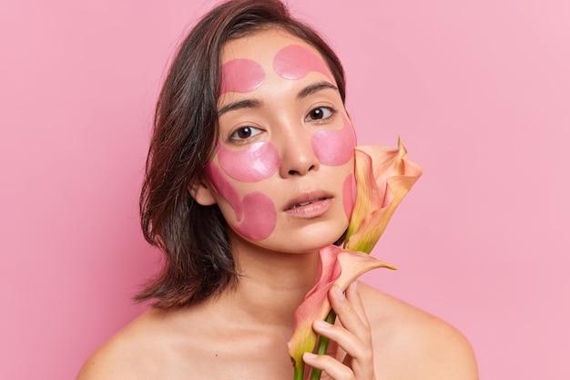 진지한 아시아 여성이 얼굴에 하이드로겔 패치를 바르고 이국적인 꽃이 회춘 노화 방지 절차를 거치며 분홍색 벽 위에 격리된 실내에서 맨 어깨를 합니다