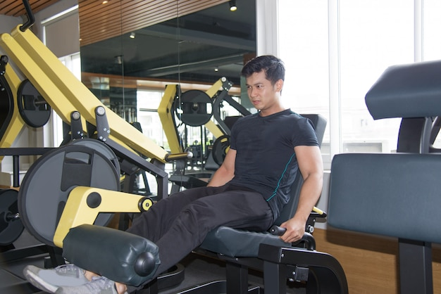 Serious asian man training legs on exercise machine
