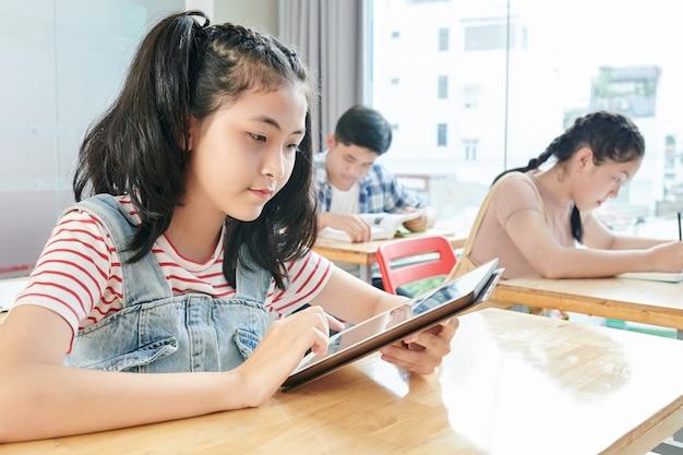 Серьезная азиатская школьница читает текст на планшетном компьютере, сидя за столом в классе