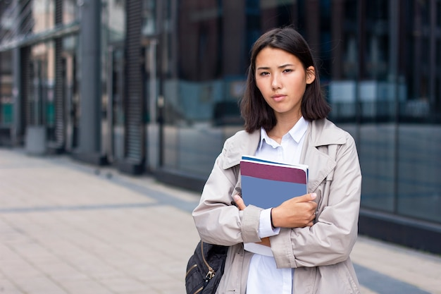 Serious asian student or chinese businesswoman standing outside office workplace with textbooks or documents.