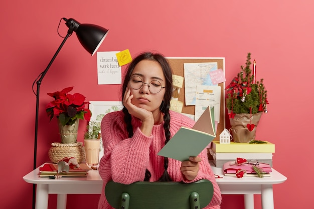 Serious asian student learns information from textbook, does school homework, wears round glasses and sweater, poses against desktop