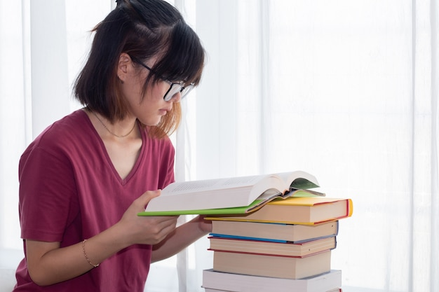 Serious asian teen girl with eyeglasses pay attention reading book for examination or competition