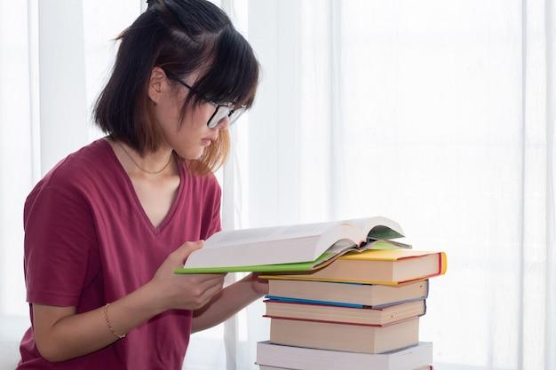 Серьезная азиатская девочка-подросток в очках обращает внимание на чтение книги для экзамена или соревнования