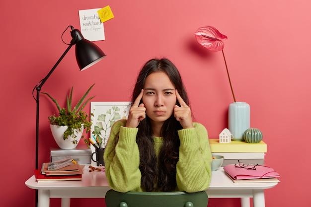 심각한 아시아 여성은 사원에 검지 손가락을 유지하고 정보를 생각하며 길고 검은 머리카락을 가지고 있으며 공동 작업 공간에 대해 포즈를 취합니다.