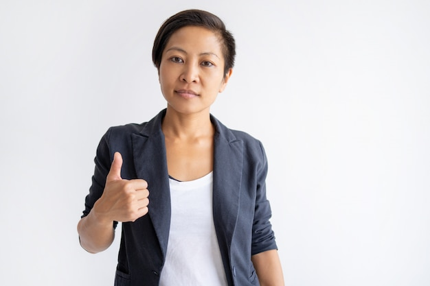 Serious asian woman showing thumb up