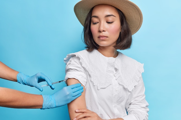 Serious asian woman in white fashionable blouse hat gets coronavirus vaccine to feel protected looks attentively at process of inoculation isolated on blue wall