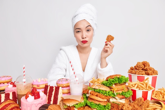 Serious asian woman with red lips healthy skin holds delicious nuggets eats tasty snacks addicted to fast food