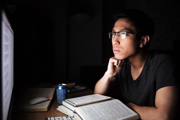 真面目なアジアの若い男が座って、暗い部屋で本やコンピューターで勉強しています