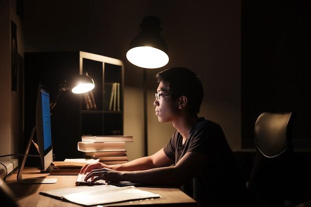 컴퓨터를 사용 하 고 어두운 방에 입력 심각한 아시아 젊은이