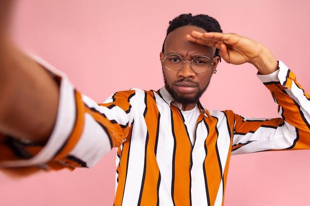 심각한 독단적 아프리카 남자 블로거, 험상, 스트라이프 셔츠에 머리 위로 손으로 멀리보고, 새로운 구독자를 찾고, 셀카 포즈. 실내 스튜디오 촬영에 고립 된 분홍색 배경