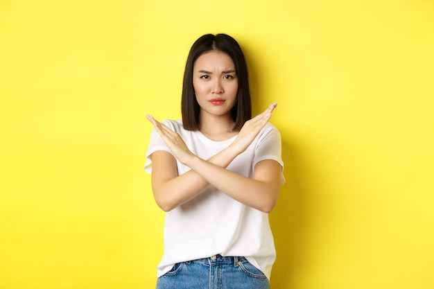 Serious and assertive korean woman showing cross stop gesture, frowning and telling no, prohibit action, disapprove something bad, standing over yellow background.