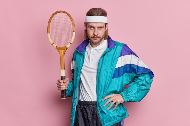 Serious athlete man holds tennis racket dressed in sport outfit looks confidently, poses against pink wall. unshaven self assured guy going to play badminton. active life concept