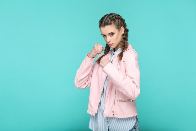 Serious attacking portrait of beautiful cute girl standing with makeup and brown pigtail hairstyle in striped light blue shirt pink jacket. indoor, studio shot isolated on blue or green background.