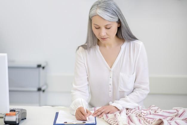 Серьезная внимательная взрослая длинноволосая женщина в белой блузке пишет информацию о документе на стойке регистрации