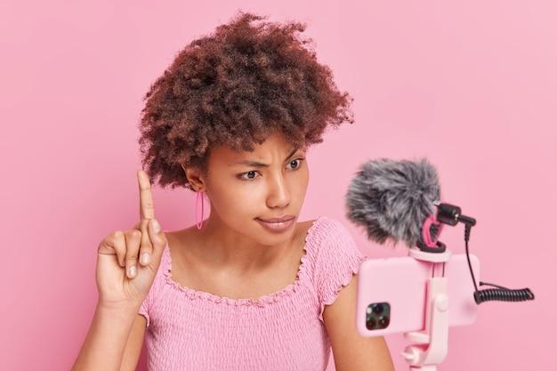 진지한 아프리카계 미국인 여성이 스마트폰 카메라에 초점을 맞춘 검지 손가락을 들어 가입자와 온라인 대화를 나누며 분홍색으로 격리된 중요한 팁을 제공합니다