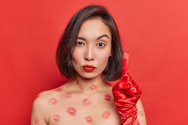Una donna asiatica seria e attenta alza il dito indice indossa i guanti sta a torso nudo con tracce di labbra indossa pose rossetto rosso al coperto ha un'idea eccellente