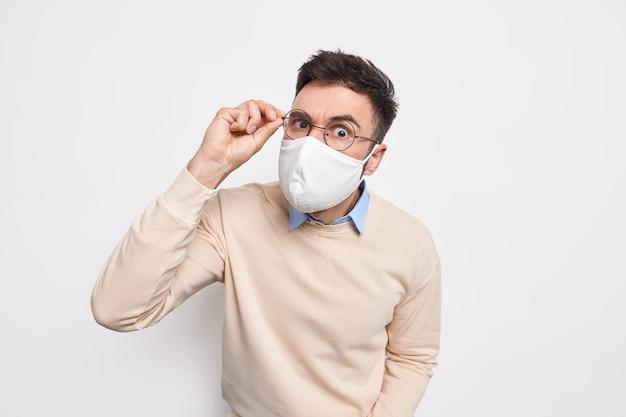Серьезный внимательный брюнет носит защитную маску в общественном месте, держит руку на очках, защищает себя от коронавируса, одетый в повседневную одежду