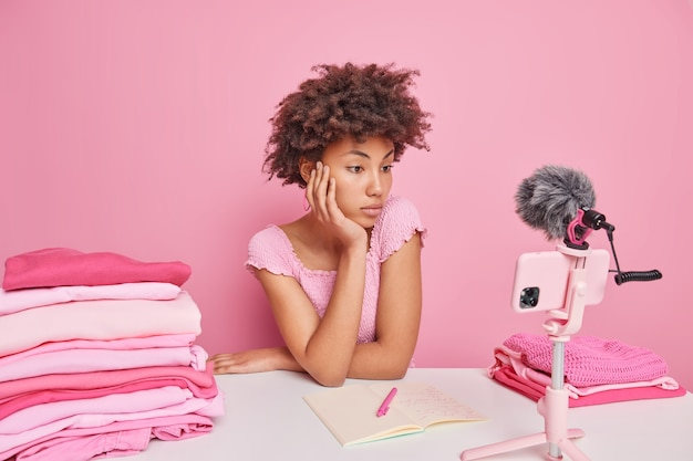 Serious attentive curly female freelancer watches video how to do washing at home sits at table with folded laundry isolated over pink