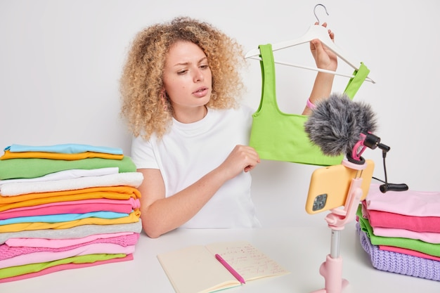 Serious attentive curly haired female entrepreneur sells clothes online advertises green top on hangers poses at table with colorful folded laundry isolated over white wall. female influencer