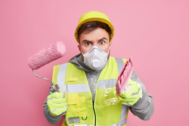 Serious attentive engineer wears helmet protective mask and safety uniform holds building equipment busy reconstructing apartment