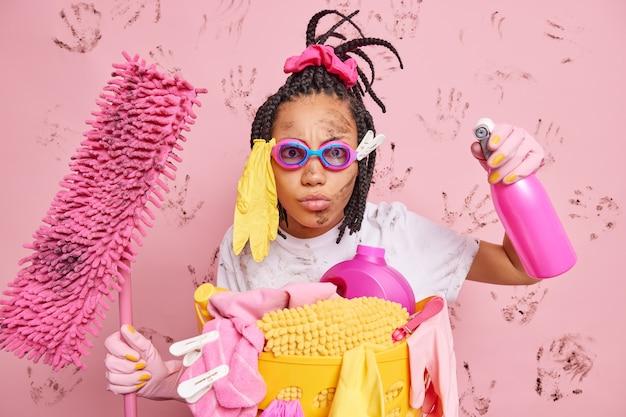더러운 얼굴을 가진 심각한 세심한 여성 가정부 세제 스프레이로 집을 소독하는 방 청소는 분홍색 벽 위에 고립 된 세탁 바구니 근처에 바닥을 씻는 걸레를 보유하고 있습니다.