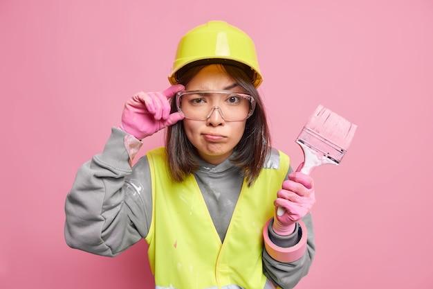 진지한 세심한 여성 유지 보수 작업자가 투명한 보안경을 손에 들고 바쁜 리모델링 집은 보호용 헬멧 유니폼을 입고 페인트 브러시를 보유하고 있습니다.