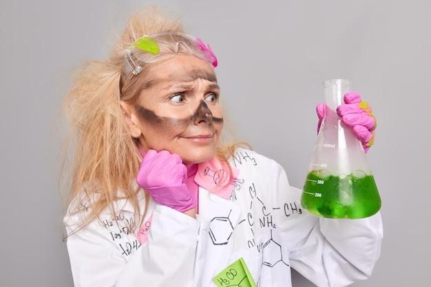 진지한 세심한 여성 약사는 흰색 코트 고무 장갑을 끼고 녹색 액체가 있는 플라스크를 들고 회색으로 격리된 놀란 표정을 보여줍니다