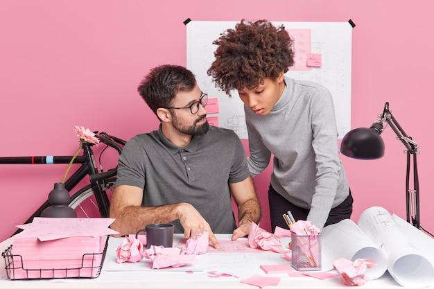 真面目で気配りのある女性と男性の同僚が協力して、建築家の注文のプロジェクトスケッチに関するエンジニアリング作業でのブレーンストーミング会議の準備をしながら、しわくちゃの紙でデスクトップでポーズをとります