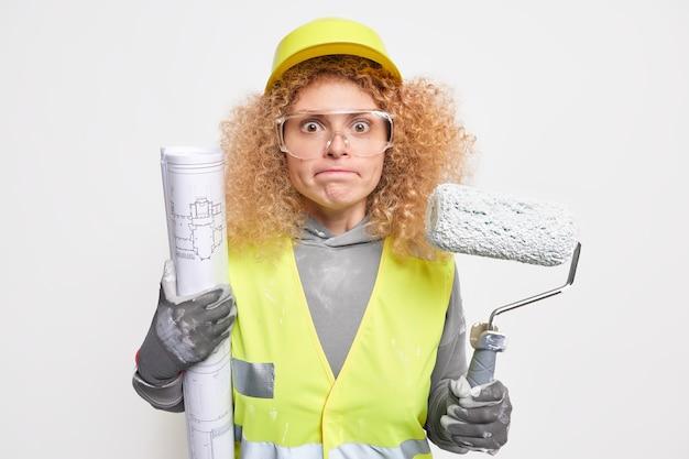 심각한 세심한 여성 엔지니어 보유 건축 청사진 및 페인트 롤러