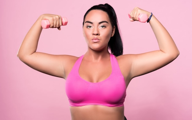 Serious attitude. portrait of brave pretty mulatto woman standing with small dumbbells in both her hands isolated