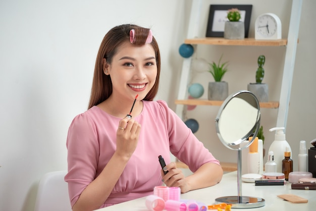 Serious attractive applying lip gloss and holding mirror in bright living room
