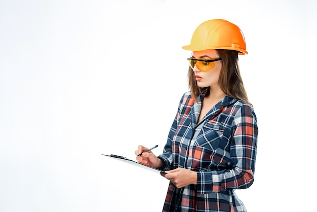 ヘルメットをかぶった真面目な魅力的な建築家の女性。白い背景で隔離。カジュアルな服装でスマート、賢い、素敵なスタイリッシュな素敵なかわいいブルネットの女の子。保護眼鏡をかけ、フォルダーを保持します。