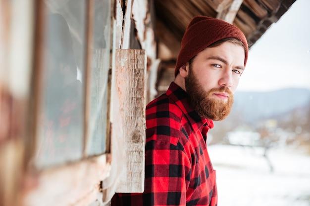 Серьезный привлекательный бородатый мужчина в старом деревянном доме в деревне