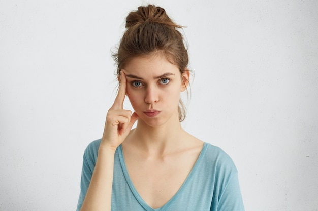 Serious attractive blue-eyed woman with hair knot wearing casual clothes holding finger on her temple having thoughtful expression.