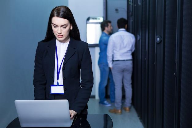 Серьезная привлекательная уверенная в себе женщина, стоящая перед ноутбуком и работающая над ним, находясь в центре обработки данных