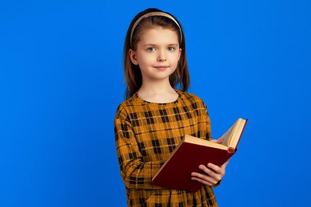 Серьезная привлекательная милая школьница держит книгу на синем фоне
