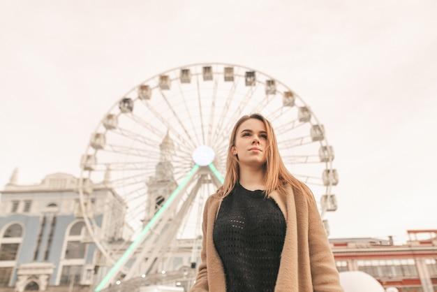 春服で深刻な魅力的な女の子、通りと観覧車の前に立って、ベージュのコートを着て楽しみにして