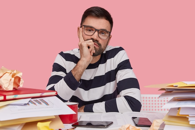 Serious attractive male freelancer looks directly at camera, keeps hand under chin, wearrs spectacles and striped sweater
