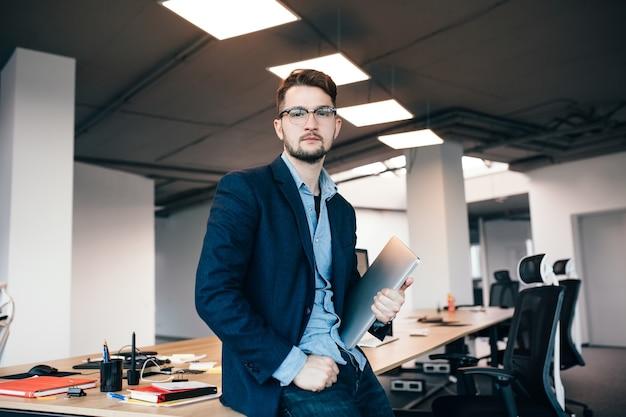 Серьезный привлекательный мужчина в очках стоит возле рабочего места в офисе. он носит синюю рубашку, темную куртку и травмированный ноутбук. он смотрит в камеру.