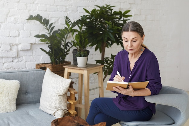 Allenatore di affari femminile maturo attraente serio che ha concentrato lo sguardo concentrato mentre scrive sul suo taccuino, fissando un appuntamento con il cliente, seduto su una sedia nell'interiore moderno