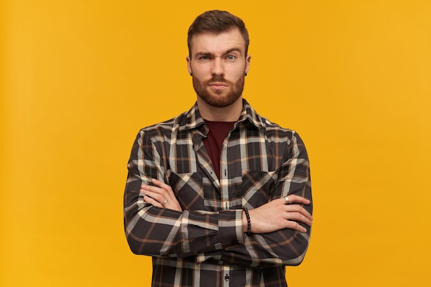 Serious attractive young bearded man in plaid shirt looks confident standing with hands folded and raised brow over yellow wall