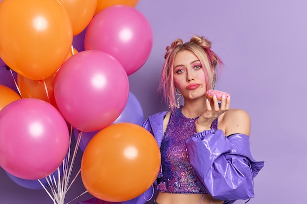 Serious attractive young european woman looks bored, dressed in fashionable purple jacket and cropped top holds tasty donut being on party poses with bunch of colorful helium balloons