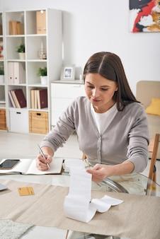 日記に経費を記録しながらテーブルに座って財務小切手を見て真面目な魅力的な若い女性