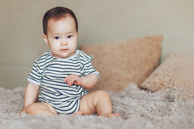 Serious baby girl sitting at bed at home. white vintage childroom. childhood concept. looking
