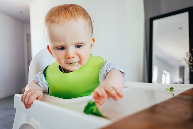 Serious baby girl sitting on highchair and grabbing finger food