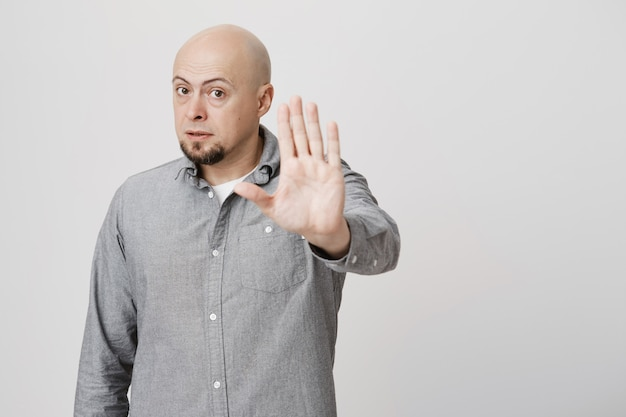 Serious bald man tell to stop, stretch hand disapproval gesture