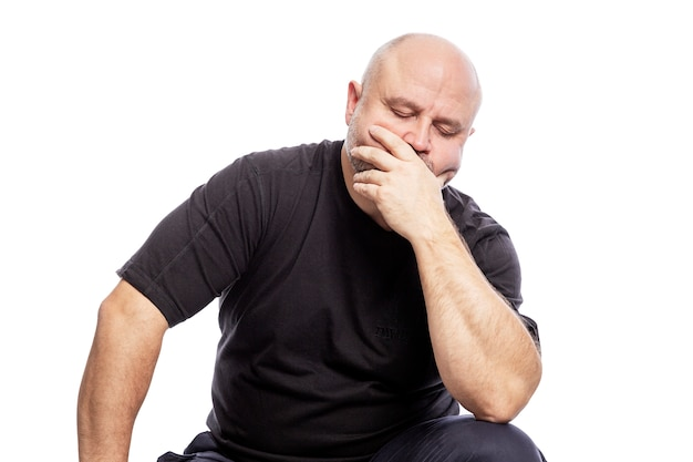 A serious bald middle-aged man in a black t-shirt is sitting with his hand in his face. isolated over white .