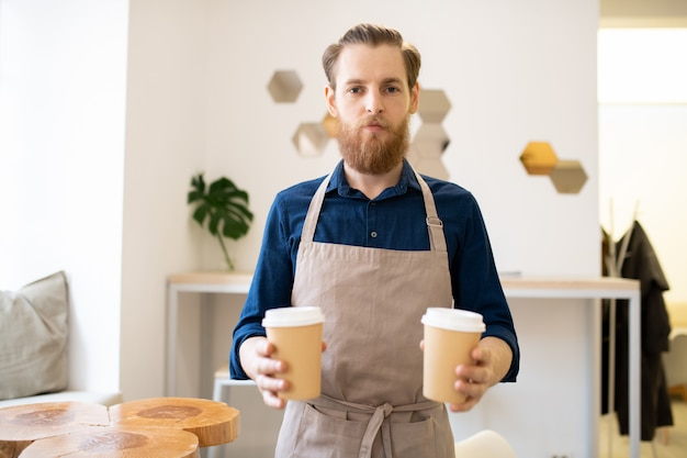 Serious barista man giving two takeout coffee cups