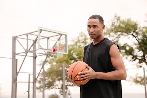 壁にバスケットボールのフープと通りに立っている深刻なバスケットボール選手